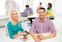 Happy colleagues having lunch and eating at office. Corporate, food and people concept - happy colleagues having lunch and eating at office royalty free stock photo