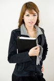 Corporate girl. A corporate girl confidently posing with her notebook Royalty Free Stock Photo