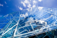Corporate glass and steel building. A bright blue sky and white clouds reflected in a modern  glass and steel skyscraper Royalty Free Stock Photography
