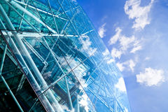 Corporate glass and steel building. A bright blue sky and white clouds reflected in a modern  glass and steel skyscraper Stock Photos