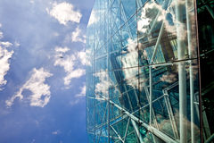 Corporate glass and steel building. A bright blue sky and white clouds reflected in a modern  glass and steel skyscraper Royalty Free Stock Photos