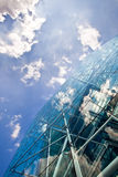 Corporate glass and steel building. A bright blue sky and white clouds reflected in a modern  glass and steel skyscraper Stock Image