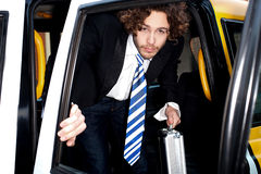 Corporate guy getting out of a taxi cab Royalty Free Stock Image