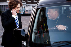Corporate guy interacting with taxi driver. Taxi cab driver communicating with male passenger Stock Images