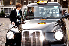 Corporate guy interacting with taxi driver Stock Image