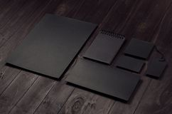 Corporate identity set of blank black letterhead, envelope, notepad, business card on dark wood board, inclined. Corporate identity set of blank black stock photos