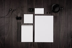 Corporate identity template, blank stationery set with coffee and earphone on black stylish wood background. Royalty Free Stock Images