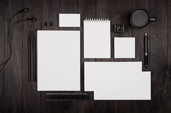 Corporate identity template, blank stationery set with coffee and earphone on black stylish wood background. Stock Images