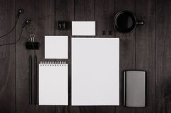 Corporate identity template, blank stationery set with coffee and earphone on black stylish wood background. Royalty Free Stock Photos