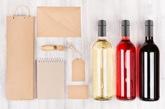 Corporate identity template for wine industry, blank brown kraft packaging, stationery, merchandise set with bottles different wi. Ne on soft white wood Stock Photos