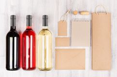 Corporate identity template for wine industry -  blank packaging, stationery set with wine bottles on soft white wood background. Stock Image