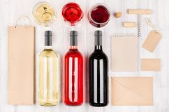 Corporate identity template for wine industry - blank packaging, stationery, wine bottles and glasses on soft white wood board. Stock Photos