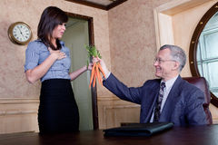 Corporate incentive program. Executive dangling carrots to his admin stock photography