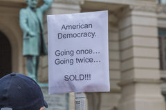 Corporate Influence Protest Sign. A person holding a protest sign at a state capitol against the influence of American corporations in politics and the stock photo