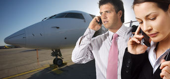 Corporate jet. Very busy young businesspeople talk on mobiles. They are on the runaway in front of a corporate jet