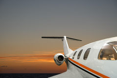 Corporate jet. Corporate private jet flying during sunset Stock Photo