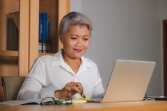 Corporate job lifestyle portrait of happy and successful attractive middle aged Asian woman working at office laptop computer desk royalty free stock photography