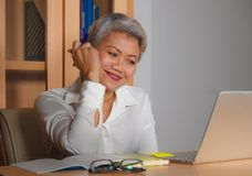 Corporate job lifestyle portrait of happy and successful attractive middle aged Asian woman working at office laptop computer desk royalty free stock images