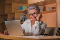 Corporate job lifestyle portrait of happy and successful attractive middle aged Asian woman working at office laptop computer desk stock photo