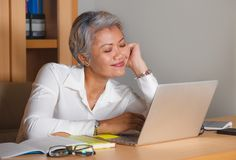 Corporate job lifestyle portrait of happy and successful attractive middle aged Asian woman working at office laptop computer desk stock photography
