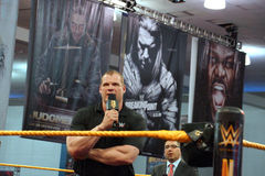 Corporate Kane talks into mic with arms crossed in ring Royalty Free Stock Photography