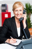 Corporate lady communicating on phone. And confirming appointment Royalty Free Stock Photo