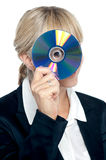 Corporate lady looking through compact disc hole Stock Images