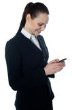 Corporate lady reading sms. On cell phone, isolated on white Royalty Free Stock Photo
