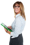 Corporate lady using big green calculator. Bespectacled businesswoman using calculator, pressing key 5 Royalty Free Stock Images