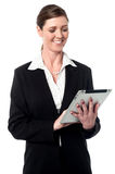 Corporate lady using a tablet device. Happy businesswoman operating her touch pad device Royalty Free Stock Images