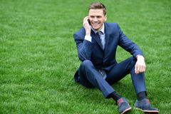 Corporate male relaxing on grass meadow Stock Photography