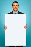 Corporate man holding big white blank billboard Royalty Free Stock Image