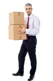 Corporate man holding stack of parcel boxes. Corporate man with a cardboard box in hand Royalty Free Stock Photography