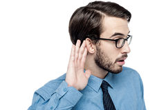 Corporate man listening with hand on ear Royalty Free Stock Photography
