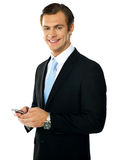 Corporate man messaging from cellphone Royalty Free Stock Photos