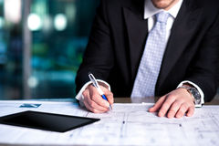 Corporate man reviewing his project plan. Cropped image of a business executive reviewing his project plan in office Stock Photography
