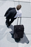 Corporate Man With Rolling Luggage. Holding His Jacket Royalty Free Stock Photos