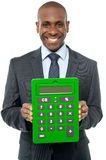 Corporate man showing big green calculator Royalty Free Stock Photography