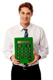 Corporate man showing big green calculator Royalty Free Stock Image
