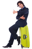 Corporate man sitting above the luggage. Showing thumbs up in isolated white background royalty free stock photos