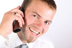 Corporate Man Smiling On The Phone. Portrait Of A Young Man In Corporate Attire Being Enthusiastic On The Phone Royalty Free Stock Photos