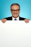 Corporate man standing behind big blank billboard Stock Photo