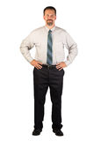 Corporate Man Standing with Hands on Hips. A white collar worker standing facing the viewer with hands firmly on hips. This man could be a spokesperson for a Royalty Free Stock Photo