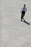 Corporate Man Walking On Pavement. Young Corporate Man Walking On Pavement With His Hand In His Pocket Royalty Free Stock Photography