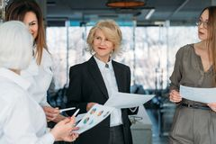 Corporate meeting successful business women. Corporate meeting. Successful mature business women standing in conference hall with graphs, discussing strategy royalty free stock photography