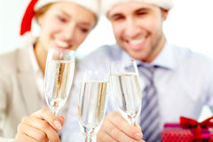 Corporate New Year. Two business people clinking glasses, the focus is on champagne flutes Royalty Free Stock Image