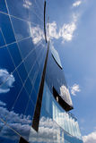 Corporate office building. Modern corporate highrise building reflecting sky with clouds Stock Image