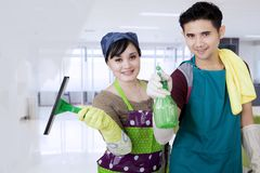 Corporate office cleaners working cleaning the window. Corporate Asian office cleaners couple with tools working cleaning the window stock images