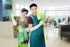 Corporate office cleaners working cleaning the window. Corporate Asian office cleaners couple with tools working cleaning the window stock photo