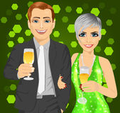 Corporate party. Business man and elegant woman celebrate with wine glasses in their hands Royalty Free Stock Photography